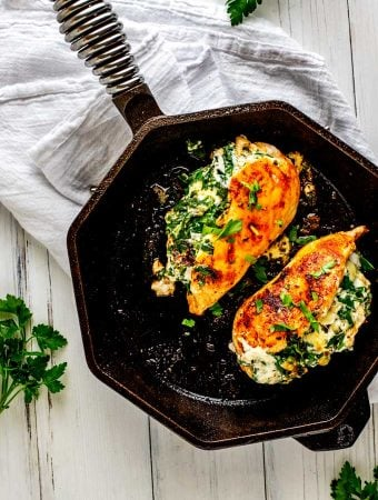 Photo of two pieces of Keto Stuffed Chicken in a cast iron skillet against a white background.