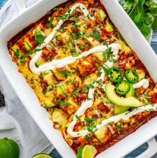 Photo of Zucchini Enchiladas in a white casserole dish garnished with sour cream and jalapeno.