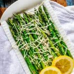 Overhead photo of Keto Asparagus on a white serving dish that is sitting on a wooden cutting board. The asparagus is garnished with Parmesan cheese and lemon.