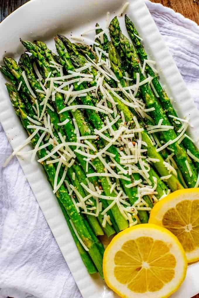 Close up photo of Keto Asparagus on a white serving dish garnished with Parmesan cheese and lemon.