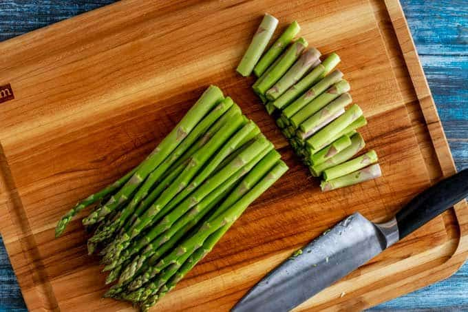 Photo of asparagus on a cutting board with the ends trimmed off.