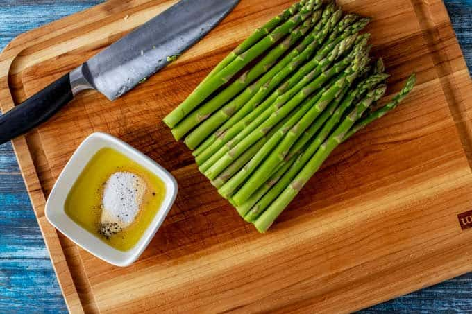 Second process shot - the oil and seasonings are being mixed together in a small bowl sitting next to the trimmed asparagus.