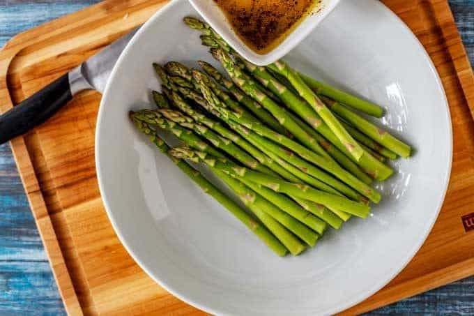 Third process photo  - oil and seasonings are being poured over the asparagus.