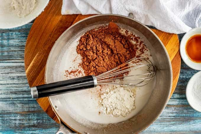 Photo of cocoa powder and swerve being mixed into warm coconut milk.