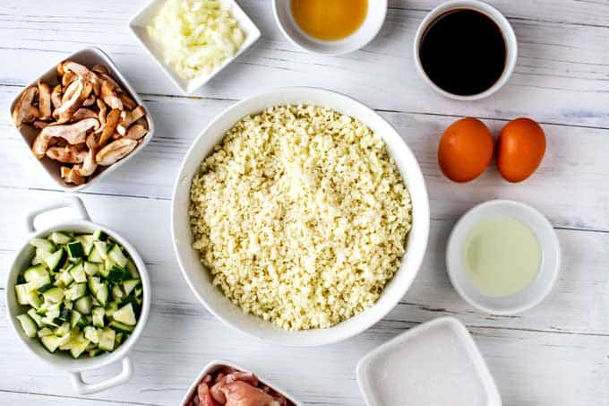 Photo of the ingredients needed for Low Carb Cauliflower Fried Rice in white prep bowls against a white background.