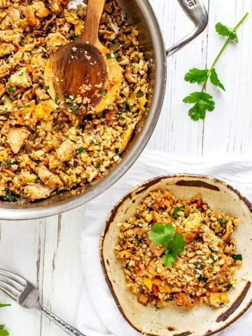 Photo of a rustic plate with Low Carb Cauliflower Fried Rice garnished with cilantro sitting next to the cooking pan.