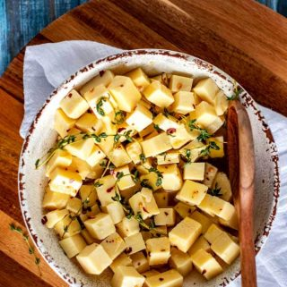 Rustic white bowl with marinated cheese cubes and a wooden spoon sitting on a white napkin resting on a wooden cutting board.
