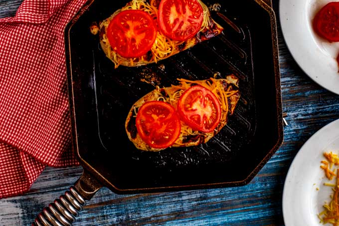 Photo of cooked chicken in a skillet with cheese and tomatoes on top of it.
