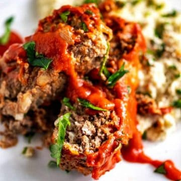 Photo of Keto Meatloaf sitting on mashed cauliflower on a white plate garnished with basil.
