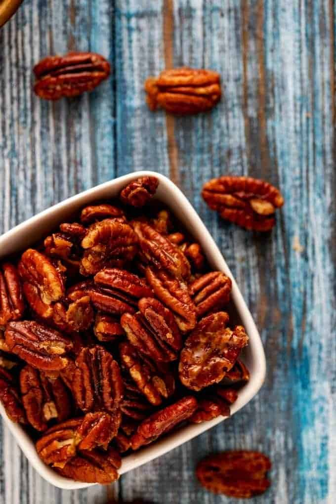 Close up overhead photo of Keto Pecans in a small white bowl sitting on a blue background with pecans scattered.