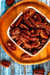 Overhead photo of Keto Pecans in a small white bowl sitting on a wooden plate against a blue background.