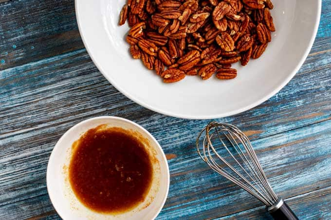 Seasoned butter sitting next to a bowl of pecans to make a low-carb pecan recipe.