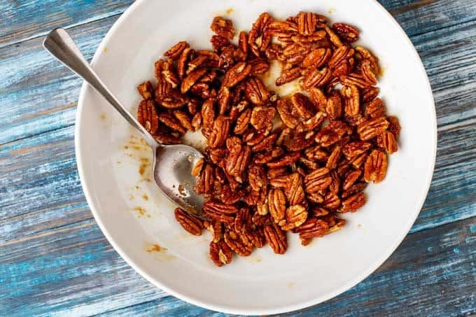 Pecans in a white bowl being coated with seasoned butter.