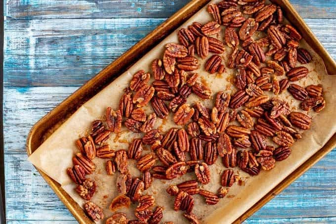 Pecans on a parchment lined baking sheet.