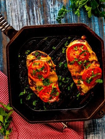 Photo of Keto Ranch Chicken in a cast iron grill pan sitting on a blue background.