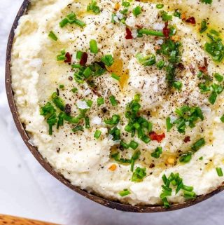 Overhead photo of low carb cauliflower mash garnished with chives, flakey salt, fresh ground pepper and crushed red pepper in a brown wooden bowl with a wooden spoon next to it.