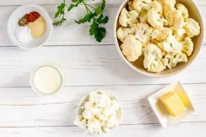Photo of a bowl of raw cauliflower, butter, goat cheese, heavy cream and seasonings.