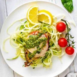 Photo of Keto Pesto Chicken sitting on a bed of zucchini noodles on a white plate with lemon and cherry tomatoes on the plate.