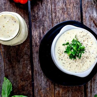 Close up overhead photo of Keto Alfredo Sauce in a small white crock on a black plate with a jar of Alfredo sauce next to it and basil, tomatoes and lemon surrounding it.