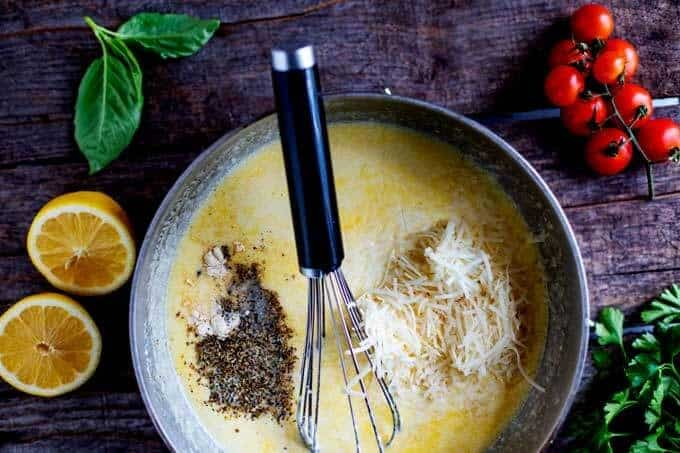 Photo of seasonings and cheese being added to melted butter, cream cheese, heavy cream, and broth.