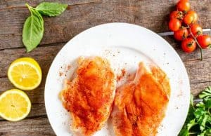 Photo of chicken breasts seasoned with cajun seasoning sitting on a white plate against a dark background.