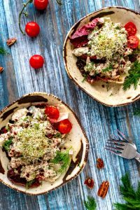 Two plates of Keto Chicken Salad toped with sprouts and garnished with dill and tomatoes sitting on a blue background.