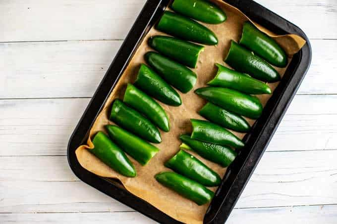 Photo of jalapeños cut in half face down on a parchment lined baking sheet.