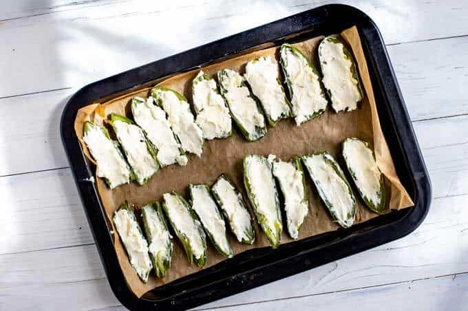 Photo of jalapenos on a parchment lined baking sheet stuffed with a goat cheese cream cheese mixture.