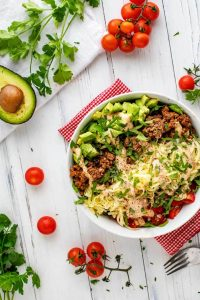 Overhead photo of a Keto Taco Salad in a white bowl sitting on a red and white napkin on a white background with an avocado half, cilantro and cherry tomatoes around it.