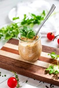Tex Mex dressing in a small glass jar with a spoon it is and cilantro on top and scattered around it.