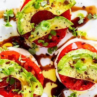 Overhead photo of a Keto Caprese Salad garnished with basil microgreens on a white plate.