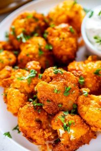 Close up photo of Keto Cauliflower Wings on a white plate garnished with parsley.