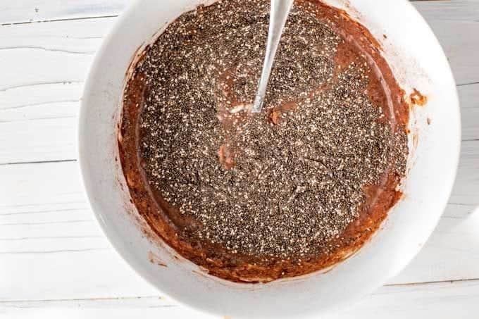 Photo of chia seeds being stirred into a chocolate mixture in a small white bowl.