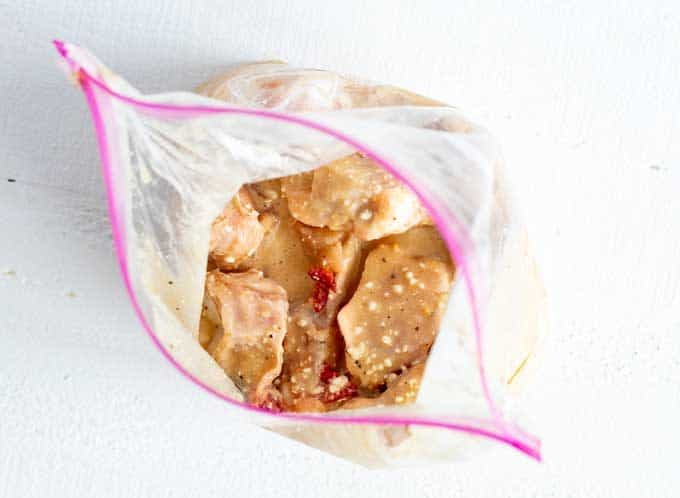 Overhead photo of chicken wings in a zip top bag with marinade poured over it.