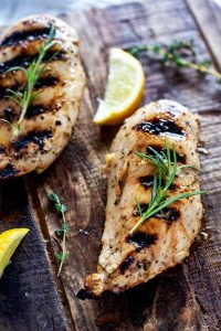 Overhead photo of keto grilled chicken on a cutting board with rosemary springs on top of it and lemons next to it.