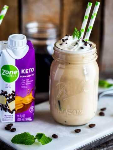 Photo of a Keto Iced Latte in a jar with two straws and a ZonePerfect Keto shake sitting next to it on a white cutting board agains a dark wooden background.
