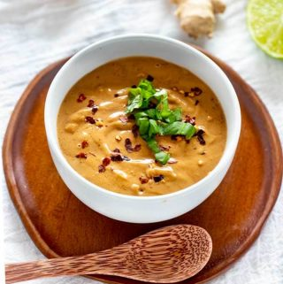 Photo of Keto Peanut Sauce in a white bowl garnished with Thai Basil and crushed red pepper flakes sitting on a wooden plate with a wooden spoon above it.