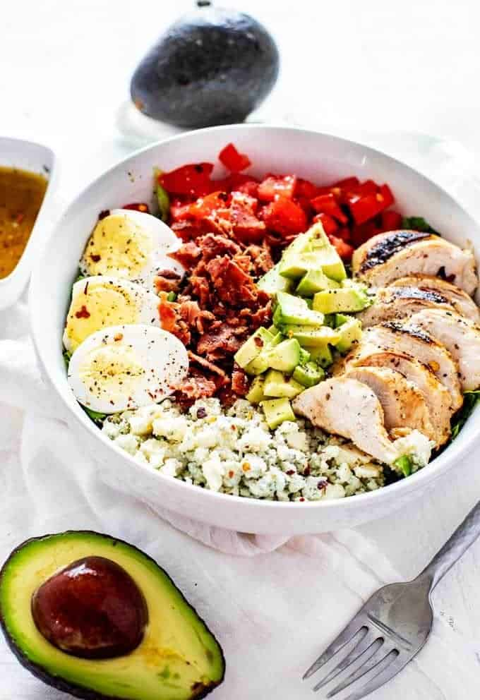 3/4 Overhead photo of a keto cobb salad in a white bowl against a white background with avocado, a fork, and dressing next to it.