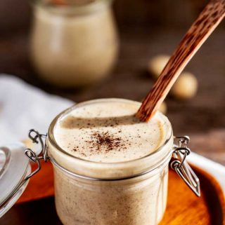 Side photo of a jar of Macadamia Nut Butter that is sprinkled with vanilla powder and has a wooden spoon in it sitting on a wooden plate with another jar and macadamia nuts sitting behind it.
