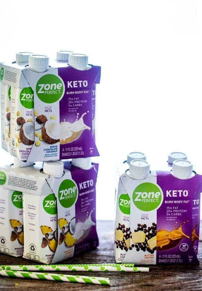 Photo of three 4-packs of ZonePerfect Keto Shakes sitting on a dark wooden board against a white background with green and white paper straws in front of the shakes.