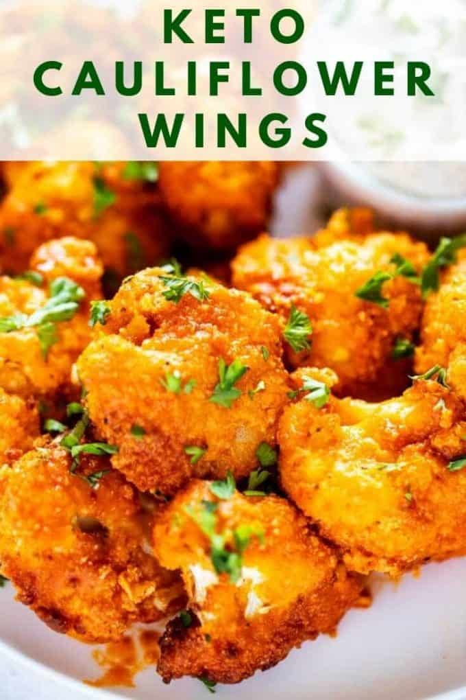 Close up photo of Keto Cauliflower wings garnished with parsley with the recipe title about the wings.