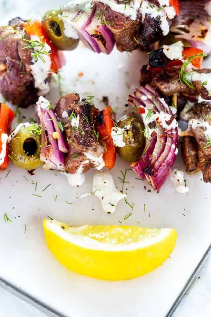 Close up photo of grilled lamb kebabs drizzled with sauce on a white plate with a lemon.