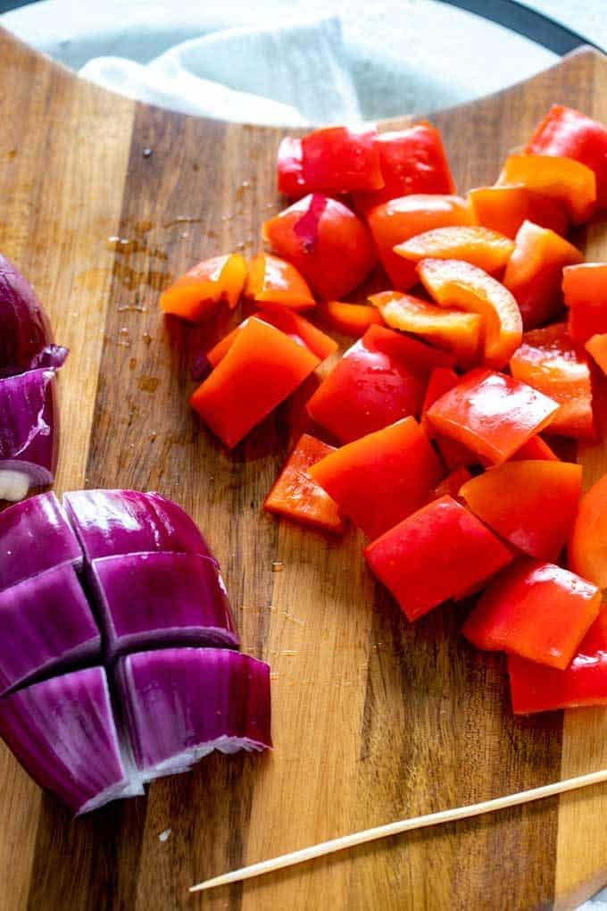 Photo of red onion and red pepper chopped on a cutting board.
