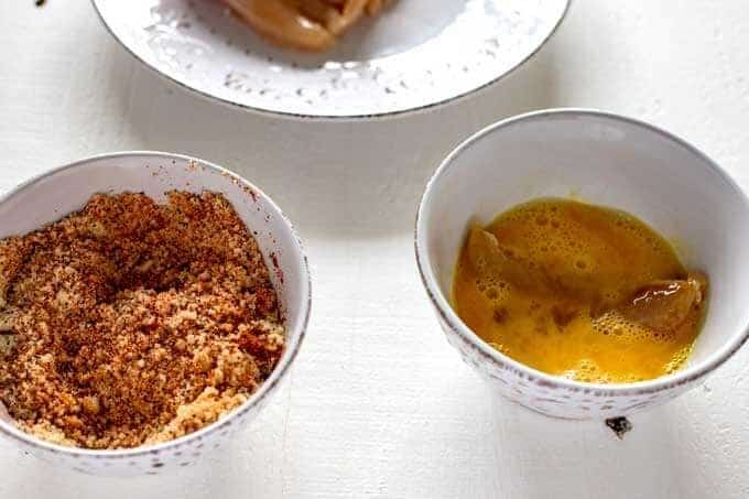 Photo of a chicken tender being dipped in an egg wash sitting next to a white bowl of Parmesan, almond flour and seasonings.