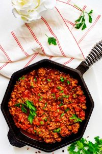Overheat photo of Keto Meat Sauce in a cast iron skillet sitting on a white back ground with a red and white napkin garnished with parsley.