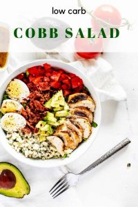 Overhead photo of a Keto Cobb Salad in a white bowl with a fork below it surrounded by tomato and avocado with the recipe title above it.
