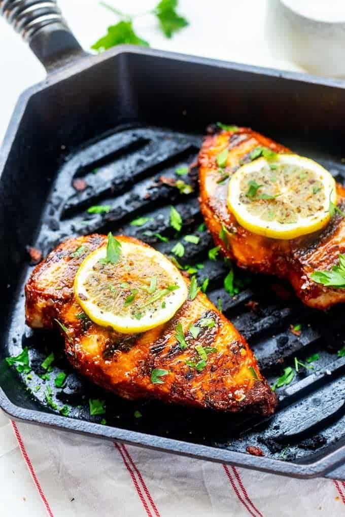 Side photo of BBQ Chicken Keto Style in a cast iron grill pan garnished with lemon slices and parsley.