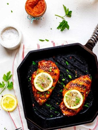 Overhead photo of Keto BBQ Chicken in a cast iron grill pan garnished with lemon and sitting on a white napkin that has red stripes.