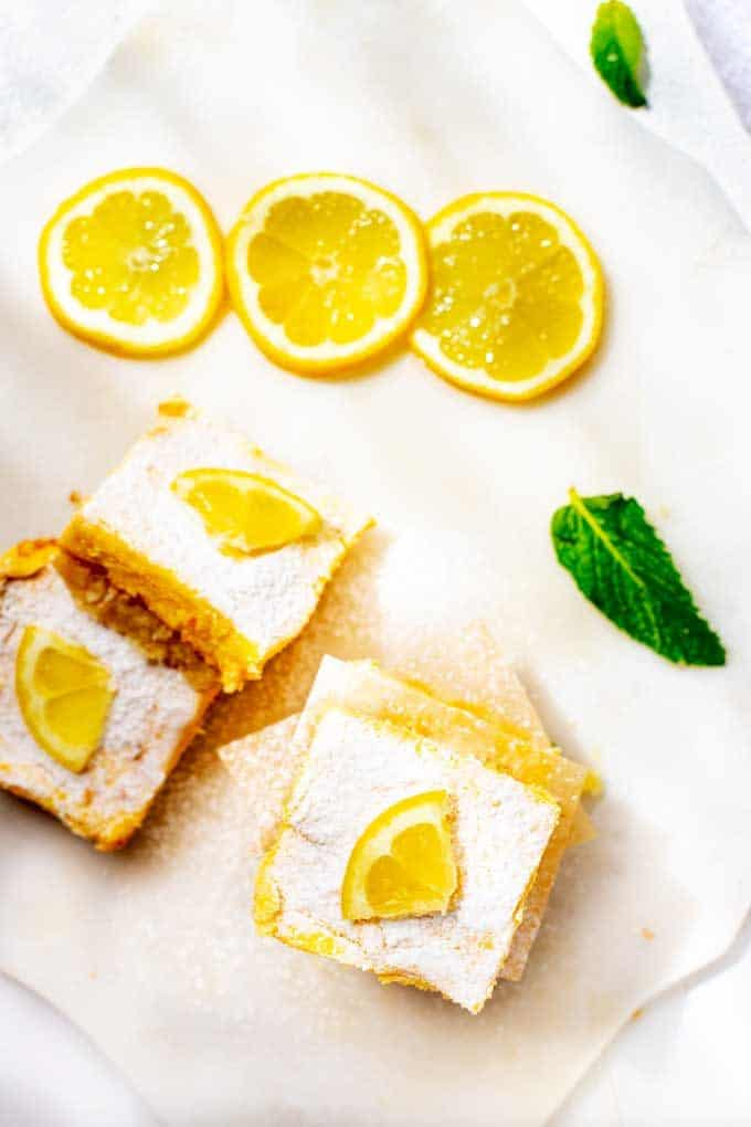 Overhead photo of Keto Lemon Bars on a white background garnished with fresh lemons.
