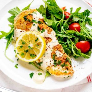 Photo of a piece of creamy Keto Lemon Chicken drizzled with lemon sauce and served over a bed of arugula.